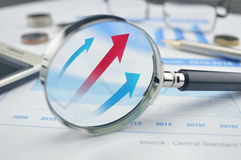 Rising red and blue arrow on magnifying glass Stock Photos