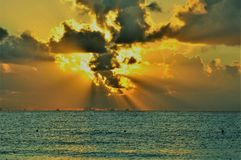 Rising at the sea. The sun in ruptures of morning clouds Royalty Free Stock Photo