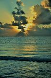 Rising at the sea. The sun in ruptures of morning clouds Stock Photos