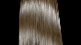 Rising and shaking of blond hair in slow motion. Isolated on black background.