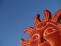 Rising Sun. A pottery figure of the Mezo-American sun god against a clear blue sky Royalty Free Stock Photos