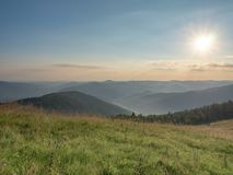 Rising sun above the dark mountain ranges. Carpathians mountains in august, west Ukraine. Early morning in grassland. Ukrainian nature landscape at summer stock image