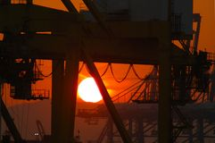 The rising sun as a white ball seen through industrial machinery. The rising sun is a white ball against an orange sky. It is silhouetted against the black of Royalty Free Stock Photography