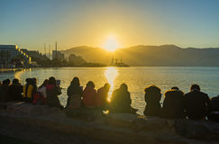 The rising sun. The beautiful sunrise over the North beach with the group of religious tourists, reading the Bible on the shore, Eilat, Israel Stock Photos