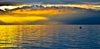 Rising Sun at Chablais Alps. Sunrise at Lake Geneva, Switzerland with Chablais Alps in the background. The low lying clouds formed at its foothills were Royalty Free Stock Image