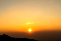 Rising sun with golden sky over mountain Stock Photos
