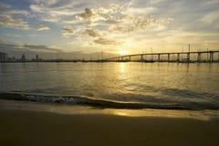 The rising sun greets Coronado Bay, San Diego, California with a warm golden light. View from Dinghy Landing on Coronado Island towards the Coronado Bridge royalty free stock photography