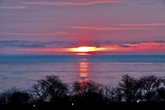 Rising Sun over Frozen Lakefront. This is a Winter picture of the sun rising over a frozen Lake Michigan Lakefront located in Chicago, Illinois in Cook County stock photography