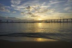The rising sun reflects warmth on calm waters in Coronado Bay, San Diego, California. View from Dinghy Landing on Coronado Island towards the Coronado Bridge stock image
