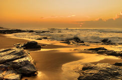 Rising sun on rocks. This is a typical South African sunrise, taken just as the sun started peeping through the clouds. The receding tide left the rocks wet Royalty Free Stock Photos