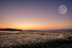 The rising sun and the setting moon. Amazing view stock image