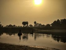 Rising sun and boats. Rising sun and two boats in the river that are operated by man royalty free stock images