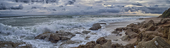 Rising tide. Panoramic on the beach where the tide is rising and break hard on the cliff takes every thrust sea Stock Photo