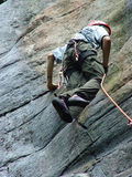 Rising to the challenge. Lead rock climber powering upwards towards Royalty Free Stock Photos