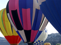 Rising Up. Hot air balloons beginning their rise from the ground Stock Photos