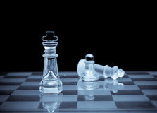 Rising Victorious. King Chess piece standing over a defeated king for business concepts of victory and success Royalty Free Stock Image