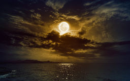 Rising yellow full moon in dark night sky with reflection in water. Dramatic mystical background - rising yellow full moon in dark night sky with reflection in stock photos