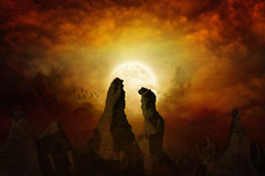 Rising yellow full moon. Dramatic mystical background - rising bloody red full moon, silhouettes of high rocks on red glowing sky. Elements of this image Royalty Free Stock Photo
