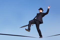Risk. Photo of careful businessman with folded umbrella on ribbon or rope running risk of falling down Royalty Free Stock Images