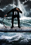 Risk. A suited man standing on a log over a raging river.  Lightening flashes in the background over the stormy waters.  Concept for risk taking and danger Stock Image