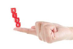 Risk. Dice labelled risk balanced on a finger tip Stock Photos