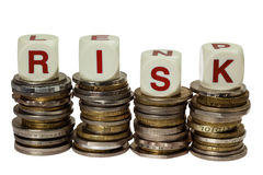 Risk. Stacks of coins with the word RISK isolated on white background Royalty Free Stock Photography