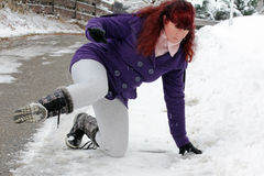 Risk of accidents in winter. A woman slipped on a snow slippery road Stock Image