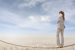 Risk, adventure, future. Chinese business woman stand on rope. Photo manipulation about risk, adventure, future or dream etc Royalty Free Stock Photos