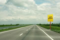 Risk ahead signage. In a rural highway with scenic clouds Royalty Free Stock Photo