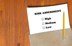 Risk Assessment Concept. Risk assessment, business planning concept, white paper and yellow pencil on brown envelope Stock Photos
