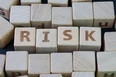 Risk assessment, decision to accept business result in uncertain. Ty, unpredictable situation concept, cube wooden block with alphabet building the word RISK Stock Photos