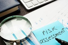 Risk assessment. Magnifying glass and documents on a table. Risk assessment concept. Magnifying glass and documents on a table royalty free stock photo