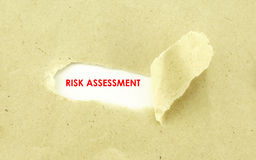 RISK ASSESSMENT. Text RISK ASSESSMENT appearing behind torn light brown envelope royalty free stock photography