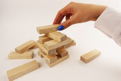 Risk assumption concept, business strategy with woman hand placing wooden pieces on a tower royalty free stock images
