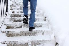 Risk av att halka, när klättra trappa i vinter royaltyfria foton