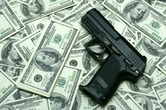 Risk business. Black gun on 100-bucks background. Clos-Up studio shot Royalty Free Stock Photography