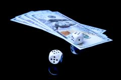Risk of business. Wooden dices and money. Devil`s bones on black mirror table. royalty free stock photos