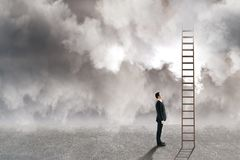 Risk and challenge concept. Young businessman looking at ladder on dull cloudy sky background. Risk and challenge concept royalty free stock images