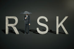 Risk concept businessman on black. Risk concept of businessman with umbrella replacing letter 'I' in word 'RISK' on black background Stock Photo