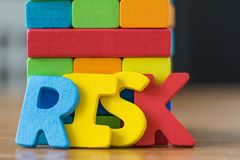 Risk concept with colorful wooden alphabets RISK and wooden bloc. Ks tower Stock Photo