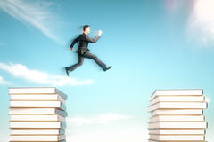 Risk concept jumpman. Risk concept with businessman jumping from one book stack onto another in blue sky Royalty Free Stock Photography