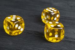 risk concept - playing dice at black wooden background. Playing a game with dice. Yellow casino dice rolls. Rolling the dice Stock Photography