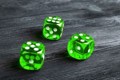 risk concept - playing dice at black wooden background. Playing a game with dice. Green casino dice rolls. Rolling the dice Stock Photo