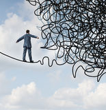Risk Confusion. Business concept with a businessman on a high wire tight rope walking towards a tangled mess as a metaphor and symbol of overcoming adversity in royalty free illustration