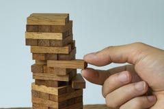 Risk eller stabilitetsbegrepp som handen som drar träkvarteret från Arkivfoton