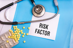 Risk factor words written on medical blue folder. With patient files, pills and stethoscope on background stock images