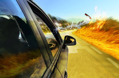 Risk of fire. Car on a road, under the hot summer sun. Somebody throws a lit cigarette butt through the open window Royalty Free Stock Image
