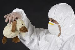 Risk of infection. A man in protective clothing holds a soft toy Royalty Free Stock Photo