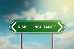 Risk and insurance on green road sign. With blurred blue sky, dark and bright side concept Stock Photo