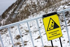 Risk of landslide sign. A risk of landslide sign in a fence with snow in the background, with the message in English and Finnish Royalty Free Stock Photography